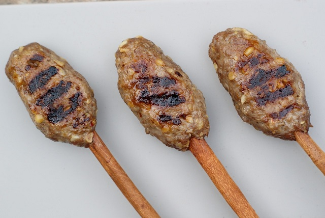 Beef and date molasses kebabs on cinnamon sticks